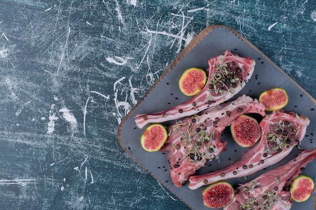 Surowe żeberka w drewnianej desce z figami i suszonymi ziołami.