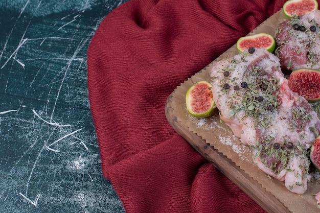 Surowe żeberka w drewnianej desce z figami, suszonymi ziołami i czerwonym suknem.