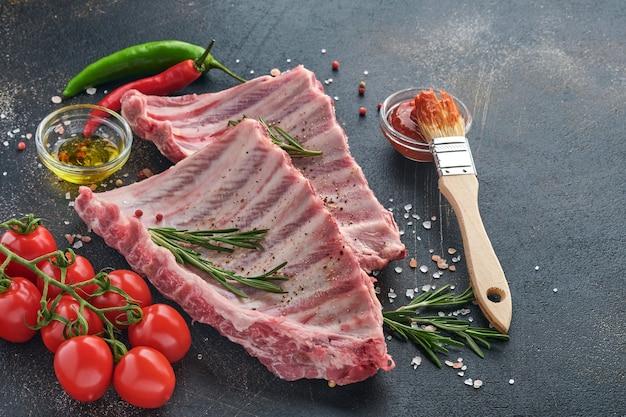 Surowe żeberka wieprzowe lub świeże, niegotowane mięso z przyprawami na czarnej drewnianej tacy z papryką, ząbkami czosnku i ziołami. ciemne tło z teksturą z miejsca kopiowania tekstu.