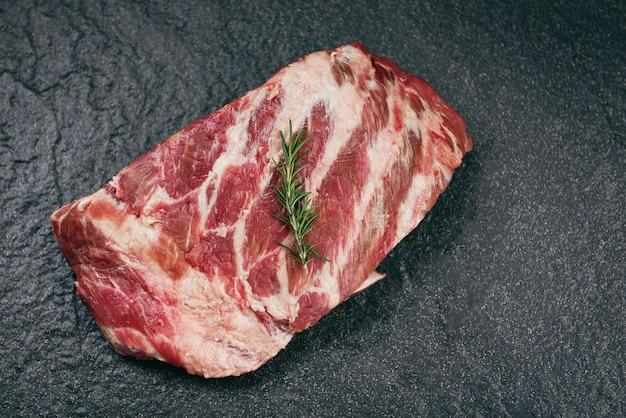 Surowe żeberka wieprzowe na czarnym tle - zapasowe żeberka wieprzowe do gotowania pieczonego lub grillowanego, kość wieprzowa z rozmarynem