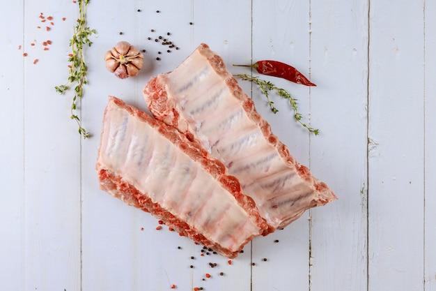 Surowe żeberka wieprzowe na drewnianej desce do krojenia z marynowanymi przyprawami z boku z czosnkiem ziele angielskie