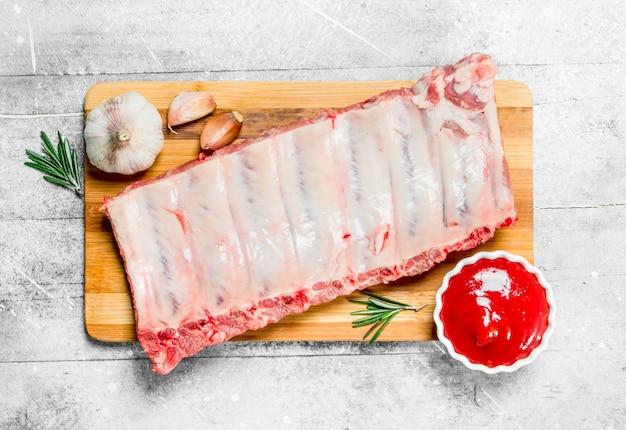 Surowe żeberka wieprzowe z przyprawami i sosem. na rustykalnym tle.