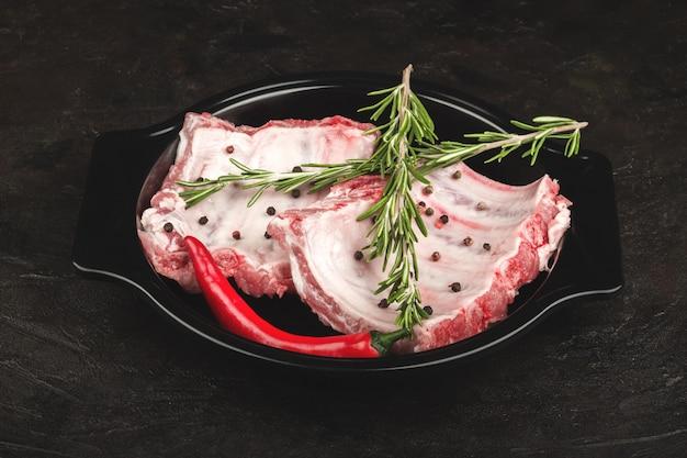 Surowe żeberka wieprzowe z rozmarynem i ostrą papryką w naczyniu do pieczenia