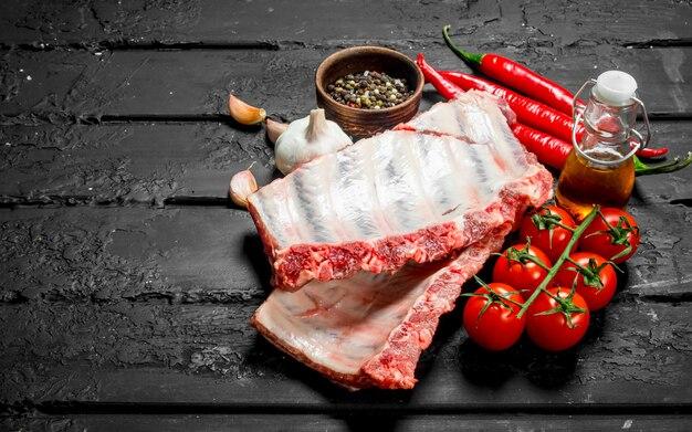 Surowe żeberka z pomidorami i przyprawami na czarnym drewnianym stole.