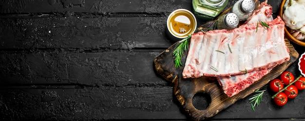 Surowe żeberka z przyprawami i sosem na czarnym rustykalnym stole.