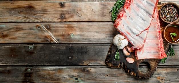Surowe żeberka z przyprawami i ziołami na drewnianym stole.