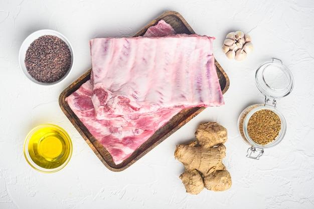 Surowe żeberka z zestawem rozmarynu i warzyw, z miodem, na białym tle, widok z góry płaski lay