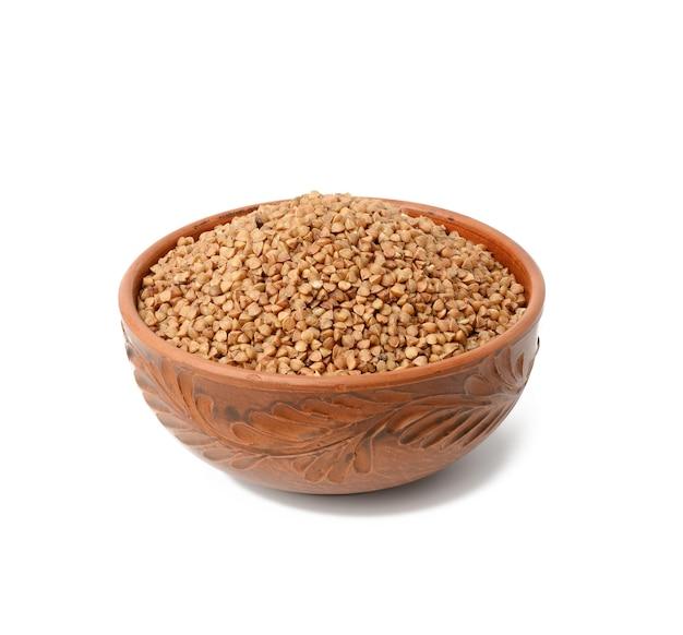 Surowe ziarna gryki w brązowy talerz ceramiczny, zboża izolowane