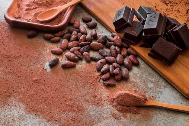 Surowe ziarna kakaowca i proszek z kostkami czekolady