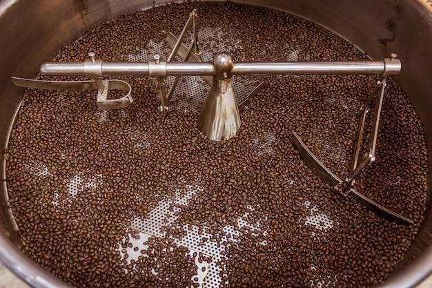 Surowe ziarna kawy w srebrnych maszynach do prażenia