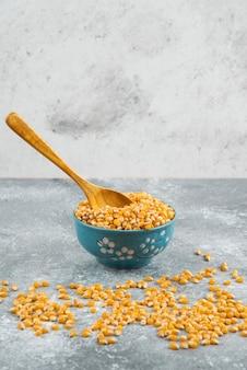 Surowe ziarna kukurydzy w niebieskiej misce z drewnianą łyżką.