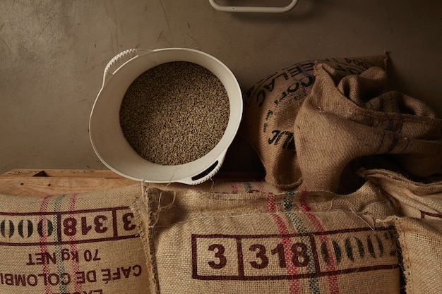 Surowe ziarna zielonej kawy z białego plastikowego koszyka