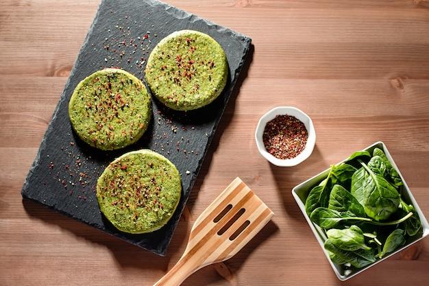 Surowe zielone burgery z kurczaka i szpinaku z przyprawami na kamiennej płycie w twardym świetle, widok z góry. zdrowe odżywianie układanie jedzenia, kopiowanie miejsca