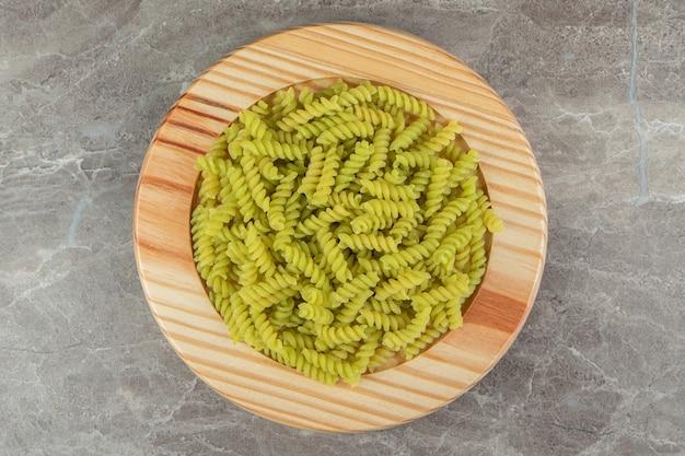 Surowe zielone fusilli na drewnianym talerzu