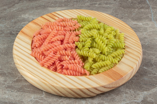 Surowe zielone i czerwone fusilli na drewnianym talerzu