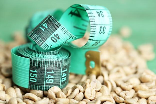 Surowe zielone ziarna kawy i taśma miernicza. pojęcie utraty wagi