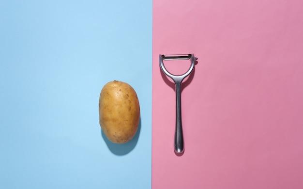 Surowe ziemniaki i nóż do obierania na różowym niebieskim tle pastelowych. widok z góry