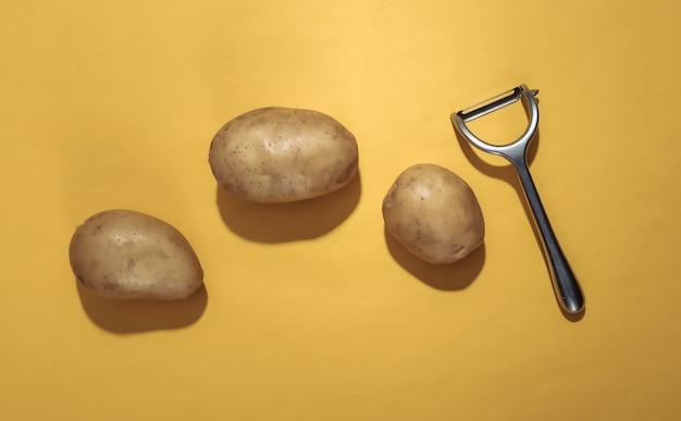 Surowe ziemniaki i nóż do obierania na żółtym tle. widok z góry
