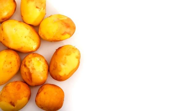 Surowe ziemniaki na białym tle. świeże ziemniaki na odosobnionym. wczesne zbiory. umyte warzywa. selektywne skupienie. pojęcie umiejętności kulinarnych. miejsce na napis lub logo