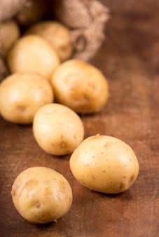 Surowe ziemniaki w torbie na drewnianym tle