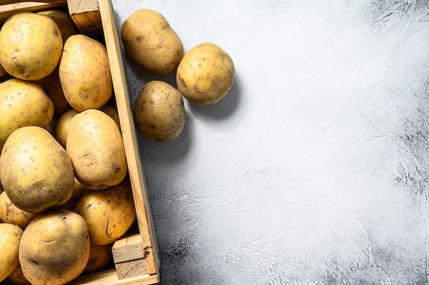 Surowe żółte ekologiczne ziemniaki w drewnianym pudełku. szare tło. widok z góry. skopiuj miejsce.