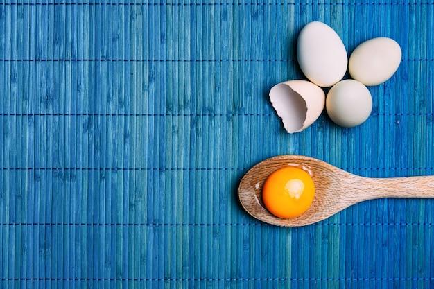 Surowe żółtko w łyżce obok jaj, na niebieskim tle ekologiczne.