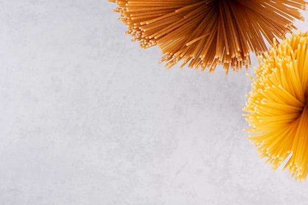 Surowe żółto-brązowe spaghetti na białej powierzchni