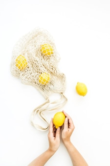 Surowej cytryny w żeńskich rękach i sznurkowej torbie na białym tle. płaskie ułożenie