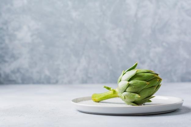 Surowi cali organicznie mokrzy zieleni karczochy nad szarym tekstury tłem.