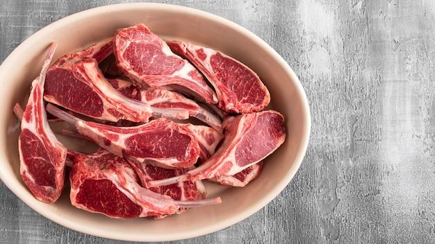 Surowi jagnięcy mięsni ziobro na talerzu z kopii przestrzenią. widok z góry.
