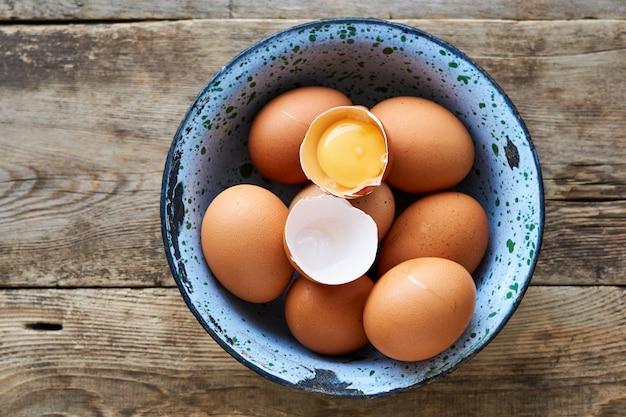 Surowi kurczaków jajka w metalu rzucają kulą na drewnie