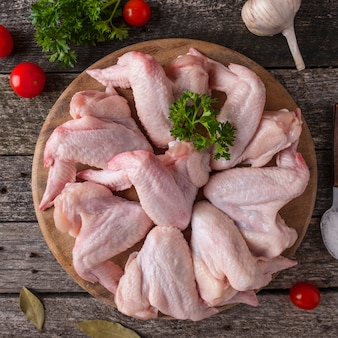 Surowi kurczaków skrzydła na drewnianej tnącej desce. widok z góry