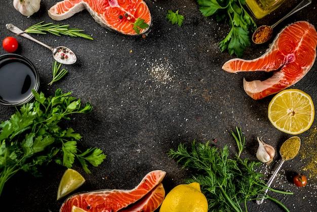 Surowi łososiowi stki rybni z cytryny ziele oliwą z oliwek przygotowywający dla grill łupku tnącej deski ciemnego ośniedziałego tła