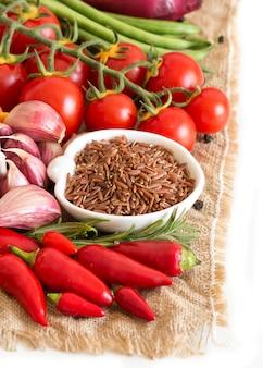 Surowi susi czerwoni ryż w pucharze i warzywach na burlap odizolowywają na bielu zakończeniu up