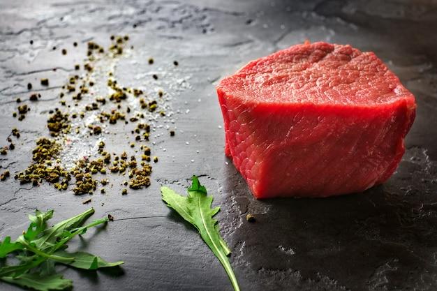 Surowi świezi marmurkowi filetów mignon stki na czerń kamienia tle