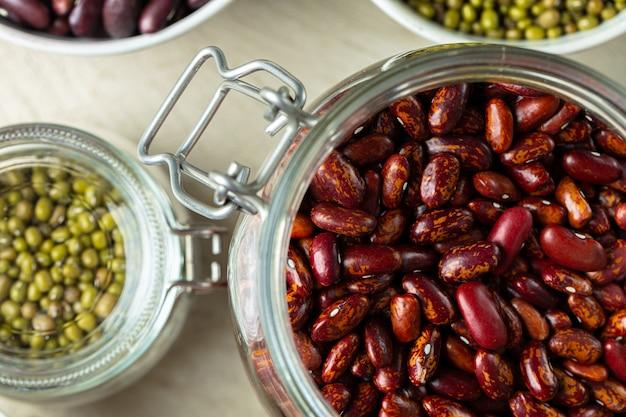 Surowi zboża lub fasole w szklanych słojach zamykają up. wegańskie i wegetariańskie jedzenie.