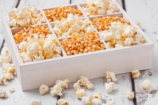 Surowi złoci słodkiej kukurudzy ziarna i popkorn w białym drewnianym pudełku na lekkim tle