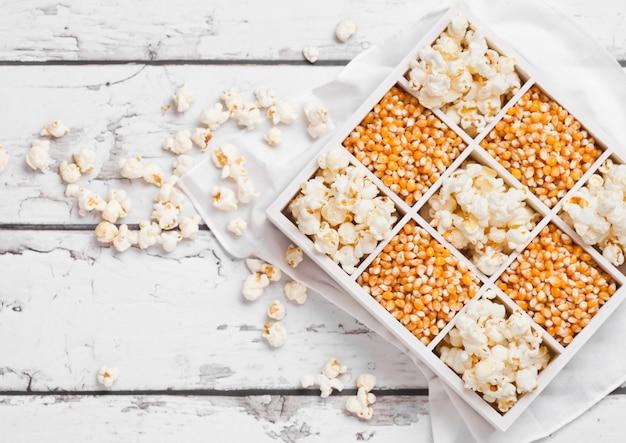 Surowi złoci słodkiej kukurudzy ziarna, popkorn w białym drewnianym pudełku na lekkim tle i odgórny widok