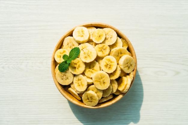 Surowi żółci bananów plasterki w drewnianym pucharze