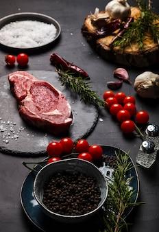 Surowy antrykot wołowy z rozmarynem, solą i pieprzem na okrągłym łupku.