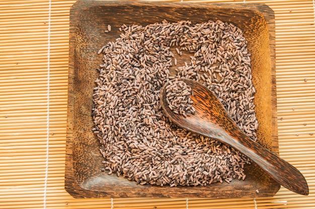 Surowy brązowy ryż na kwadratowym drewnianym talerzu i drewnianą łyżką na bambusowej serwetce