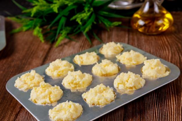Surowy brazylijski serowy chleb na patelni z olejem.