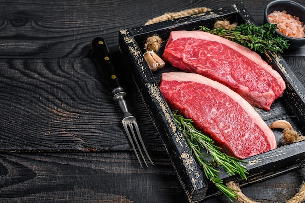 Surowy brazylijski stek picanha lub stek z polędwicy wołowej na drewnianej tacy. czarne drewniane tło. widok z góry. skopiuj miejsce.