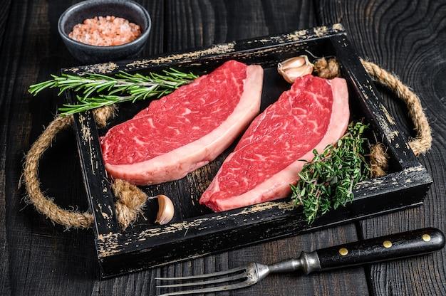 Surowy brazylijski stek picanha lub stek z polędwicy wołowej w drewnianej tacy na drewnianym stole. widok z góry.