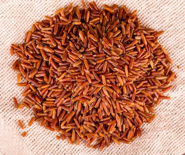 Surowy brown ryż l na parcianym tle.