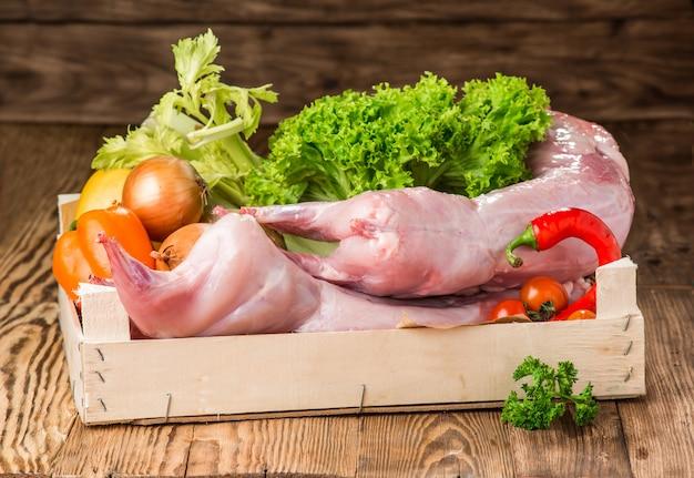 Surowy cały królik z warzywami i przyprawami
