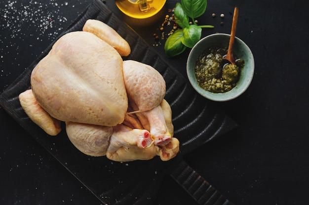 Surowy cały kurczak kukurydziany z przyprawami na ciemnym stole