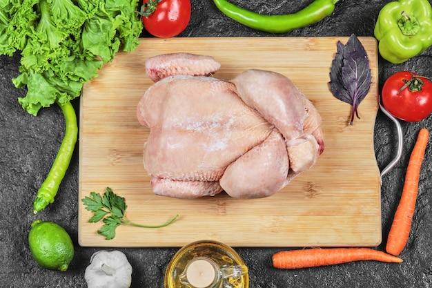 Surowy cały kurczak na desce z sałatą, papryką, oliwą i pomidorami