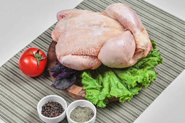 Surowy cały kurczak na drewnianym talerzu z sałatą, pomidorem i przyprawami