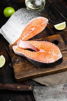 Surowy cały zestaw krojonego łososia, na starym ciemnym drewnianym stole w tle